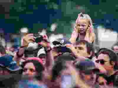 A young girl in the crowd covers her ears during the performance by American band Testament on day two of the Heavy Montreal music festival at Jean-Drapeau park in Montreal on Saturday, August 8, 2015.