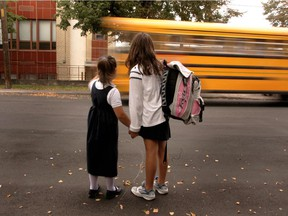 Two girls wait for a school bus in Montreal.