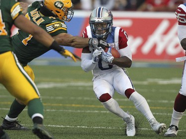 Montreal Alouettes kick returner Stefan Logan breaks a tackle by Edmonton Eskimos Mathieu Boulay during Canadian Football League game in Montreal Thursday August 13, 2015.