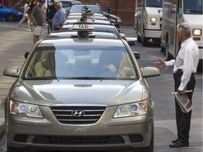 Montreal taxis and drivers, wait in line in front of Place Ville-Marie on Cathcart St. on Thursday Aug. 20, 2015.