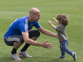 Impact star defender Laurent Ciman opens his arms to greet his 1-year-old son, Achille, after practice in Montreal on Aug. 3, 2015.