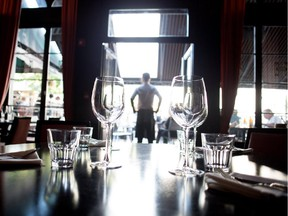 A waiter watches out over the terrace from the main dining room at Harlow Supper Club in Montreal on Tuesday August 4, 2015.