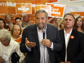 """NDP Leader Tom Mulcair, speaks to his supporters from the campaign office of NDP Courtenay-Alberni candidate, Gord Johns,(left), during a campaign stop in Parksville, B.C., on Tuesday, Aug. 18, 2015. It's becoming apparent to those who've covered him in the past that Mulcair's """"angry Tom"""" persona has been absent from this campaign - so far."""