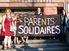 From left to right: Sophie Crepeau, Estelle Guérin (kid), Anna Kruzynski and Fanny Perret hold a banner in front of École Charles-Lemoyne, on Tuesday September 1, 2015, in Montreal, Quebec. Parents and teachers joined in  a common protest against school budget cuts.