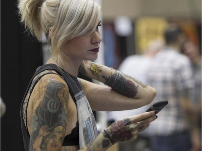 Sophie Liset uses her phone while enjoying the art tattoo show held in Montreal on Friday September 11, 2015. The show at Place Bonaventure goes on through the weekend.