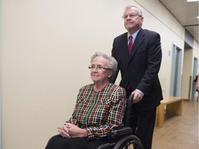 Former Quebec lieutenant governor Lise Thibault is pushed by aide Real Cloutier, Wednesday, September 30, 2015 at the courthouse in Quebec City.