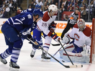 Montreal Canadiens goalie Carey Price makes a save as Toronto Maple Leafs' Dion Phaneuf (3) and Canadiens' Jeff Petry (26) look for a rebound during second period NHL action in Toronto on Wednesday, Oct. 7, 2015.