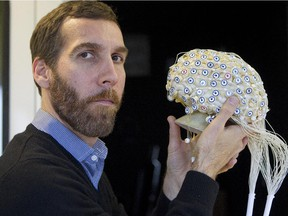 In this file photo, Dave Ellemberg , a neuropsychologist and professor at Université de Montréal, shows how an electrodes sensor net can record brain activity in his lab on Nov. 13, 2013.