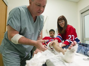 Nurse Pierre Ouellet, left, removes a cast from the leg of Marc-Étienne Pigeon, 18, while Pigeon's mother, Marie-France Boulet, right, watches, at the Shriner's Hospital's new location at the Glen Campus in Montreal, Monday October 5, 2015.  Patients were moved to the new location today for the first time and Pigeon was the first patient to be moved in.