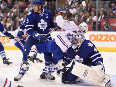 Toronto Maple Leafs' Dion Phaneuf (3) defends as Montreal Canadiens' Dale Weise (22) falls into Maple Leafs goalie James Reimer during third period NHL action in Toronto on Wednesday, Oct. 7, 2015.