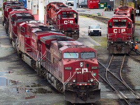 A Canadian Pacific Rail maintenance worker climbs onto a locomotive at the company's Port Coquitlam yard east of Vancouver, B.C.