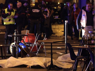 A victim is pictured on the pavement outside a Paris restaurant, Friday, Nov. 13, 2015. Police officials say dozens have been killed in shootouts and other violence around Paris. Police have reported shootouts in at least two restaurants in Paris. At least two explosions have been heard near the Stade de France stadium, and French media is reporting of a hostage-taking in the capital.
