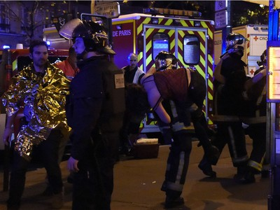 Rescuers workers evacuate a woman near the Bataclan concert hall in central Paris, on November 13, 2015. A number of people were killed and others injured in a series of gun attacks across Paris, as well as explosions outside the national stadium where France was hosting Germany.