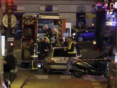 Ambulance workers are seen at the scene in the 10th arrondissement of the French capital Paris, following a string of attacks, on November 13, 2015. At least 18 people were killed as multiple shootings and explosions hit Paris, police said. Police also said there was an ongoing hostage crisis in the Bataclan a concert hall in the French capital.