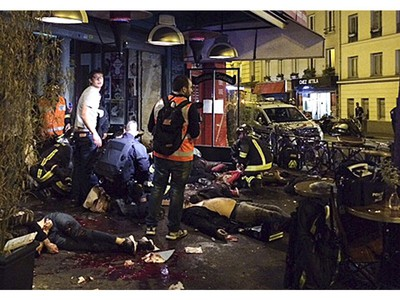 Victims of a shooting attack lay on the pavement outside La Belle Equipe restaurant in Paris Friday, Nov. 13, 2015.  Well over 100 people were killed in Paris on Friday night in a series of shooting, explosions.