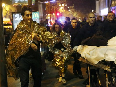 Victims walk away outside the Bataclan theater in Paris, Friday Nov. 13, 2015. Well over 100 people were killed  in a series of shooting and explosions explosions. French President Francois Hollande declared a state of emergency and announced that he was closing the country's borders.