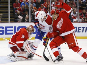 Red Wings goalie Petr Mrazek stops a shot as Canadiens' Lars Eller tries for a rebound as Red Wings defenceman Alexei Marchenko, right, defends in the third period of an NHL hockey game Thursday, Dec. 10, 2015 in Detroit.