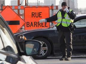 File photo: A police officer directs traffic to Girouard Ave. from St-Jacques St. in Montreal, on Monday, March 23, 2015. A section of St. Jacques, a major thoroughfare to get downtown, will be closed for 2.5 years.