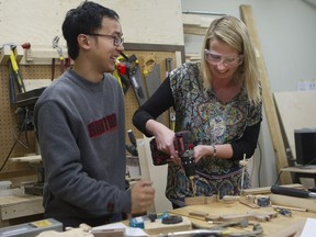 Ernest Fung shows student Valerie Fréchette how to make a wooden toy for Christmas at La Remise, a tool library in Villeray that offers its members tools from its catalogue, plus work space and classes.
