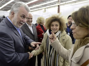 Quebec Premier Philippe Couillard greets newly arrived Syrian refugees at a St-Laurent welcome centre on Saturday, Dec. 13, 2015.