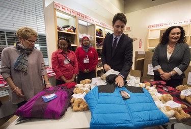 Canadian Prime Minister Justin Trudeau, second right, and Ontario Premier Kathleen Wynne, left, over look winter wear that will be handed out before they greet refugees from Syria at Pearson International airport, in Toronto, on Thursday, Dec. 10, 2015.