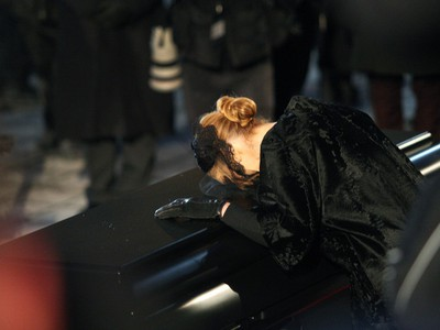 Singer Celine Dion, puts her head on her husband's coffin before getting into the limousine in front of  Notre Dame Basilica in Montreal on Friday January 22, 2016.