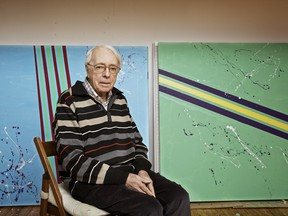 Marcel Barbeau in front of two of his paintings.