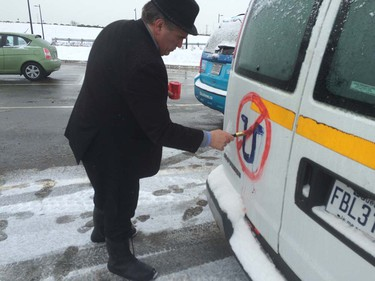 A driver paints an anti-Uber symbol on the back of van during a Montreal-wide protest Feb. 10, 2016.