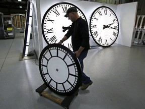 Dan LaMoore wheels a clock away from the test area as it is prepared to be shipped to a Tennessee school at the Electric Time Company in Medfield, Mass., Thursday, March 10, 2016. We will lose an hour of sleep this weekend, but gain an hour of evening light for months ahead, as daylight saving time returns this weekend. The time change officially starts Sunday at 2 a.m. local time.
