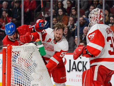 MONTREAL, QC - MARCH 29:  Mike Brown #13 of the Montreal Canadiens and Niklas Kronwall #55 of the Detroit Red Wings swing at each other near Red Wings goaltender Jimmy Howard #35 during the NHL game at the Bell Centre on March 29, 2016 in Montreal, Quebec, Canada.