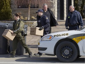 Sûreté du Québec, RCMP and Canada Border Services agents carry boxes from a house in Sainte-Marthe-sur-le-Lac, north of Montreal, March 30, 2016, as part of an operation against tobacco smuggling.