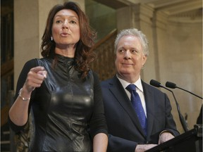 Nathalie Normandeau gestures as Jean Charest looks on during a press conference in Quebec City Tuesday September 6, 2011. Normandeau announced that she was resigning as MNA, minister, and Deputy Premier after 14 years in the Quebec Liberal Party.