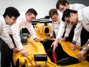 Infiniti Engineering Academy students look over a Formula One Renault racer.