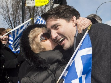 Prime Minister Justin Trudeau is hugged by a member of the crowd as he attends the Greek Independence Day parade in Montreal, Sunday, April 3, 2016.