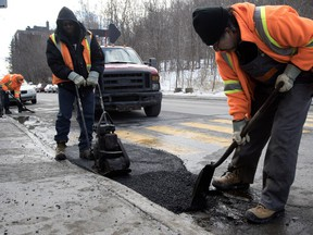 A city of Montreal road crew repairs a pothole on Cedar Ave. in Montreal, on Monday February 1, 2016.