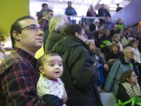 Afshin Rezaei and his daughter Adrein take in the sights during a presentation at an open door event at the N.D.G. Cultural Centre and Benny Library in Montreal Saturday, February 6, 2016.
