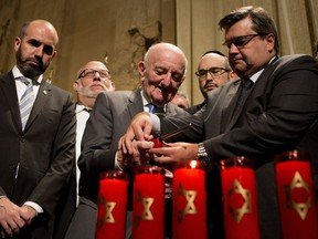 Montreal mayor Denis Coderre helps Eric Bissel light one of six candles during a Holocaust commemorative ceremony to mark Yom HaShoah, Holocaust Remembrance Day, at Montreal city hall on Wednesday May 4, 2016. Bissel and his family managed to escape Europe to the Dominican Republic in 1942 avoiding capture by the Nazis. His family came to Canada in 1948.