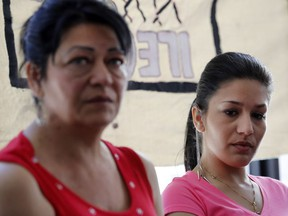 Gilda Lakatos, right, listens as her mother, Katalin Lakatos, describes the harassment that led to her son taking his own life. Lakatos was speaking at a Solidarity Across Borders press conference in Montreal on Monday May 9, 2016.