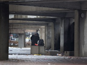A man takes shelter from the rain at Viger Square, where many homeless people camp, in Montreal, Tuesday April 8, 2014.