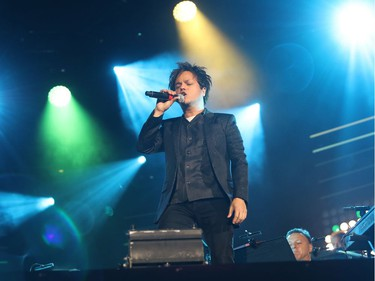 Jamie Cullum stands on the piano during the second of three big free outdoor blowout concerts at the Montreal International Jazz Festival on July 4, 2016.