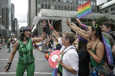 A roller derby player high-fives parade watchers during the Montreal Pride Parade as it goes through Rene-Levesque boulevard in downtown Montreal on Sunday, August 14, 2016.
