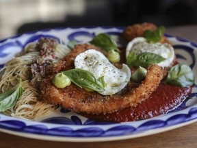 The chicken parmesan is a plate-sized chicken paillard, pan-fried to a golden crisp and topped with two rounds of fresh mozzarella, with a twirl of spaghettini and deep-red tomato sauce in the supporting roles.