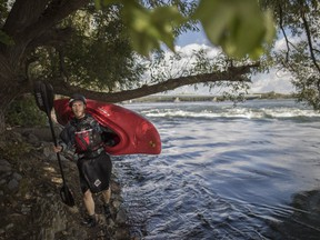 Sylvain Pelletier walks along the shore of the St. Lawrence River as he enjoys one of his vacation days to kayak on a warm early fall day in Montreal on Tuesday, Sept. 27, 2016. Earlier this year, a U.S. environmental group placed the St. Lawrence on its annual list of the most endangered rivers.