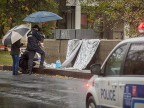 Police examine and photographic evidence at the scene of an overnight stabbing that has left a 15-year-old boy dead on Nuns' Island in Montreal, on Saturday October 29, 2016.