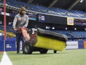 Simon Larouche levels the filling for the artificial turf at Montreal Olympic stadium on Thursday March 31, 2016. Montreal is hosting pre-season games of Major League Baseball on Friday and Saturday. The Toronto Blue Jays will meet the Boston Red Sox. (Pierre Obendrauf / MONTREAL GAZETTE)