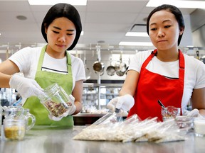 """McGill students Mengyin Hong, left, and Zoey Li prepare portions for their Yumibox customers. """"Instead of being another resource for knowledge, we're actually delivering something practical to people,"""" Li says."""
