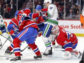 Montreal Canadiens goalie Carey Price concentrates on the puck despite being bumped by Vancouver Canucks Jannik Hansen during second period of National Hockey League game in Montreal Wednesday Nov. 2, 2016.