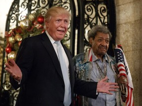 President-elect Donald Trump, left, stands with boxing promoter Don King as he speaks to reporters at Mar-a-Lago, Wednesday, Dec. 28, 2016, in Palm Beach, Fla.