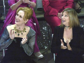 In this March 23, 2003, file photo, Meryl Streep, left, and Barbra Streisand applaud on stage during a reunion of past Oscar winners during the 75th Academy Awards in Los Angeles. Streisand told MSNBC Hardball host Chris Matthews on Monday that she completely agrees with Streep's criticisms of Trump during the Golden Globes on Sunday, Jan. 8, 2017.