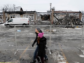 Richard Perey and Catherine Verardo walk past the site of a fire that gutted a neighbourhood mall in the Vimont district of Laval, north of Montreal on Tuesday January 10, 2017.